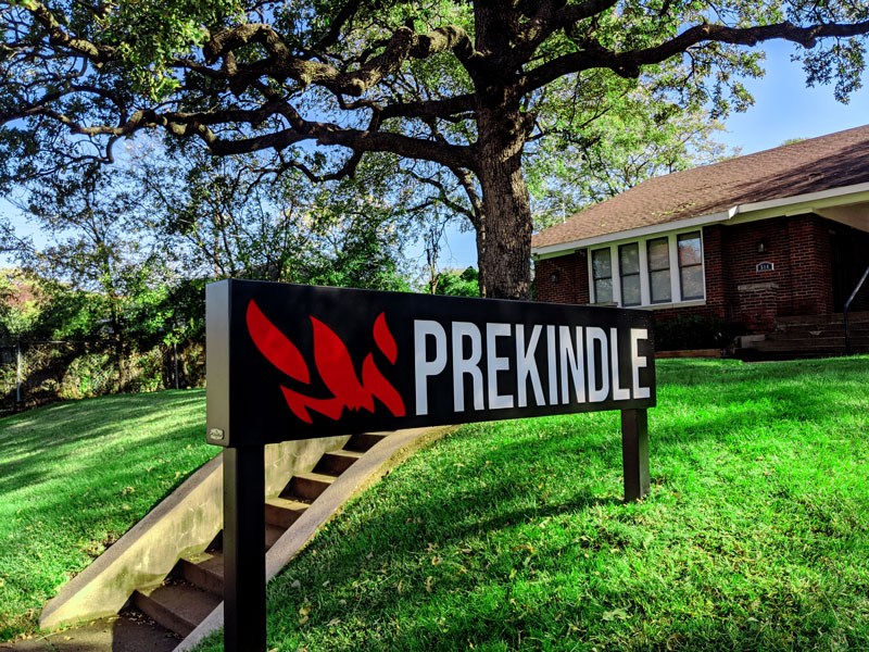 Outdoors photo of Prekindle headquarters, trees, grass, sign with logo
